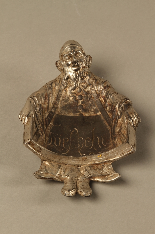2016.184.47 front Metal ashtray in the form of a Jewish man holding a tray