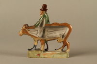 2016.184.53 back Terracotta figurine of a Jewish peddler with an underfed cow  Click to enlarge