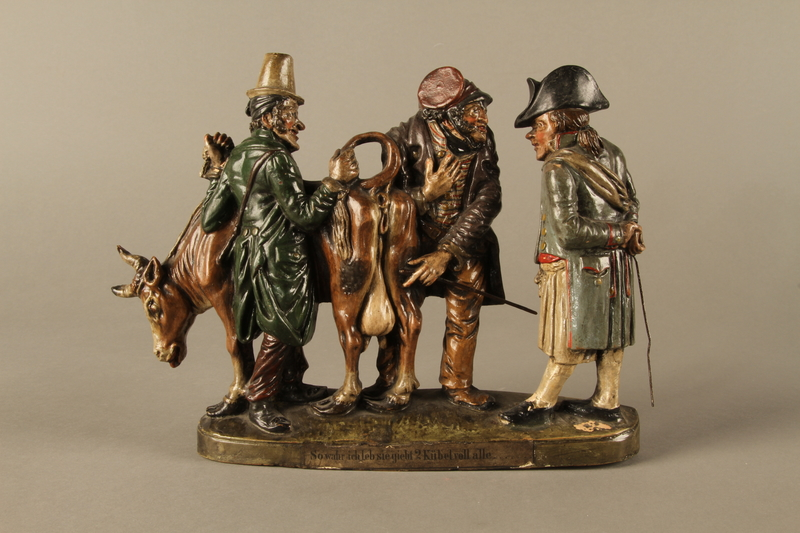 2016.184.54 front Terracotta figure group of 2 Jewish traders selling an old sagging cow