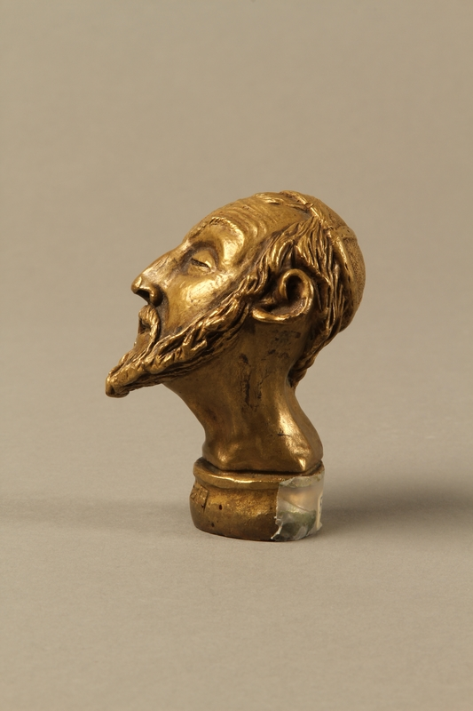 2016.184.66 left side Bronze cane knob in the shape of a squinting Jewish man's head