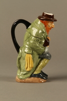 2016.184.68 right Porcelain pitcher of a seated Fagin clutching his treasure box  Click to enlarge