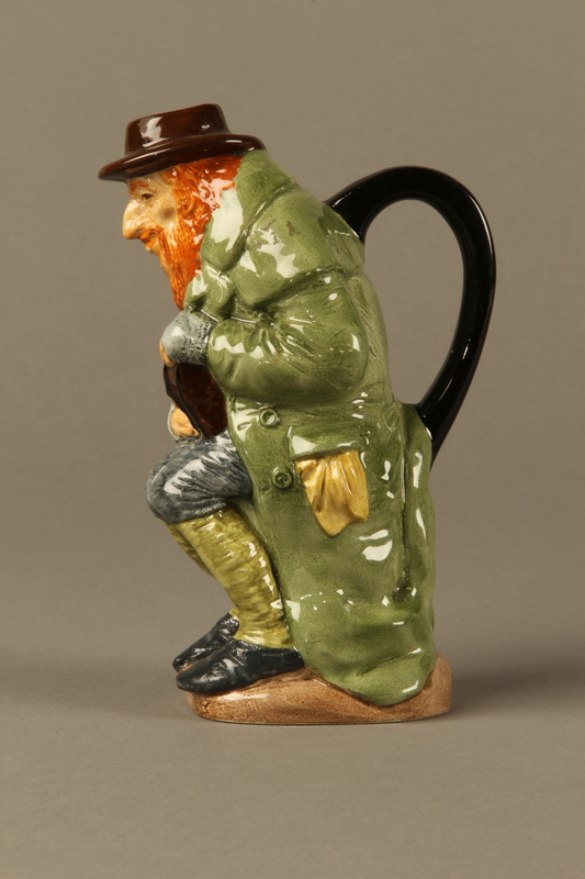 2016.184.68 left Porcelain pitcher of a seated Fagin clutching his treasure box