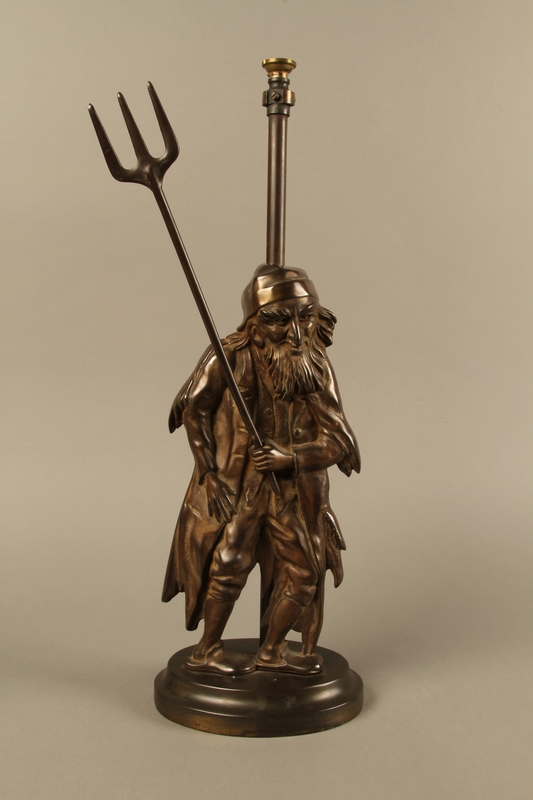 2016.184.73_a-b front Cast iron Fagin lamp holding a toasting fork / trident