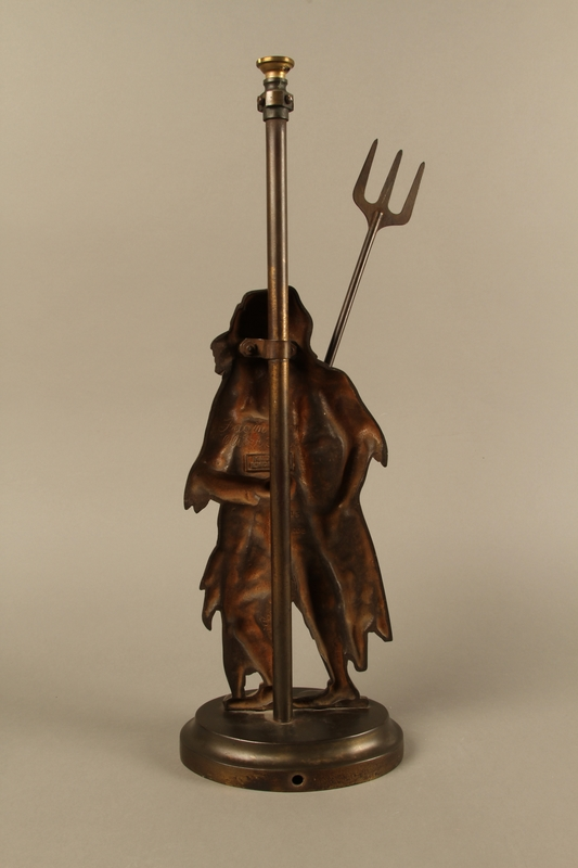 2016.184.73_a-b back Cast iron Fagin lamp holding a toasting fork / trident