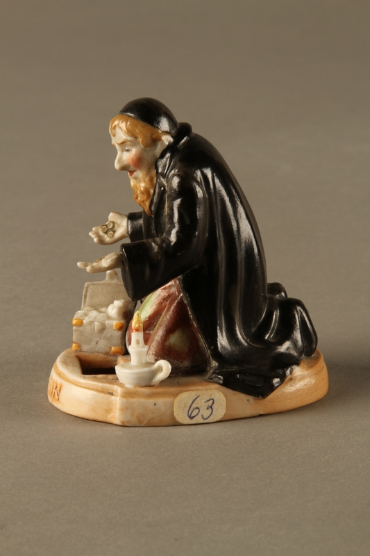 2016.184.74 left side Porcelain figure of Fagin counting his money secretly at night