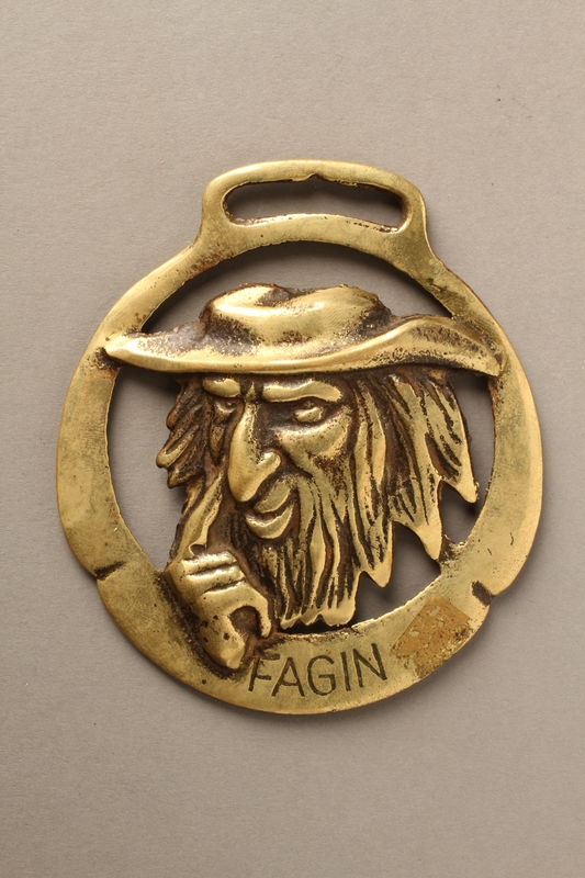 2016.184.91 front Brass horse medallion with Fagin touching his finger to his nose