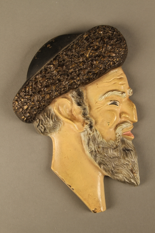 2016.184.90  front Painted metal wall bust of a sneering Jewish man in a shtreimel