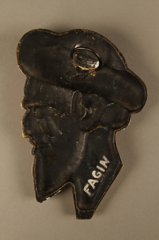 2016.184.90 back Painted metal wall bust of a sneering Jewish man in a shtreimel