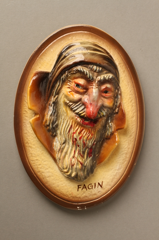 2016.184.94 front Painted ceramic wall plaque of a grostesque, grinning Fagin