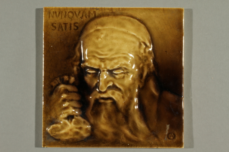 2016.184.98 front Ceramic tile with an impression of a miserly Jew holding a money bag