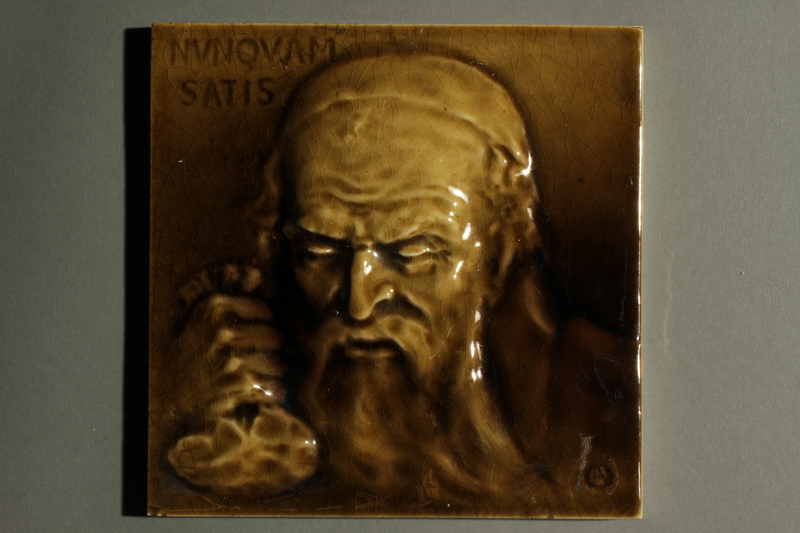 2016.184.98 front raking Ceramic tile with an impression of a miserly Jew holding a money bag