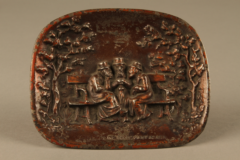 2016.184.99  front Copper painted metal dish with bas relief of 3 Jewish men on a bench