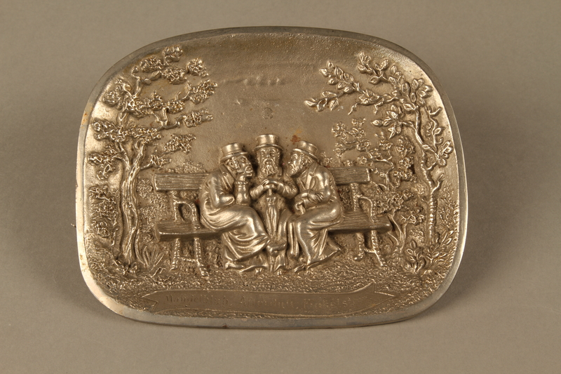 2016.184.101 front Silver colored iron dish with bas relief of 3 Jewish men on a bench
