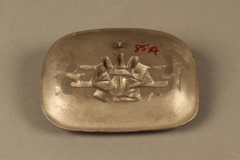 2016.184.101 back Silver colored iron dish with bas relief of 3 Jewish men on a bench