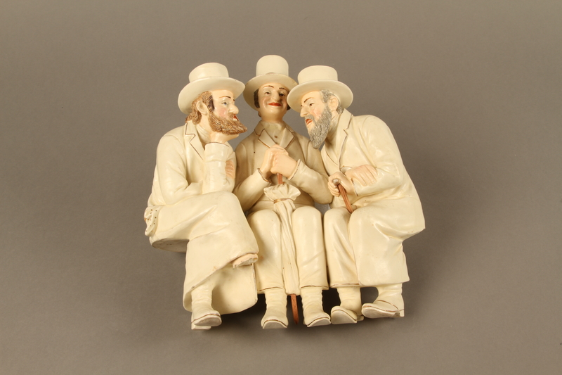 2016.184.103_a front White painted white ceramic group of 3 Jews on a bench with their umbrellas