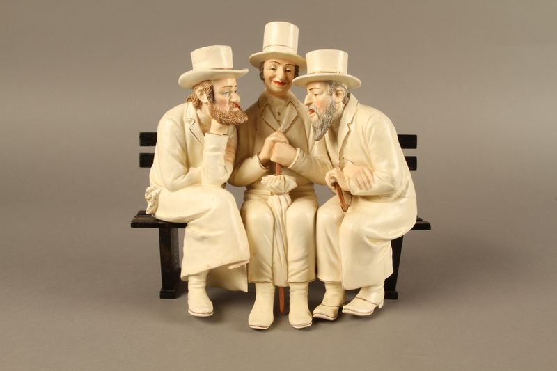 2016.184.103_a-b front White painted white ceramic group of 3 Jews on a bench with their umbrellas