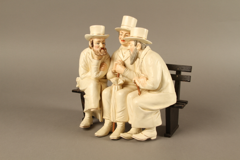 2016.184.103_a-b left side White painted white ceramic group of 3 Jews on a bench with their umbrellas