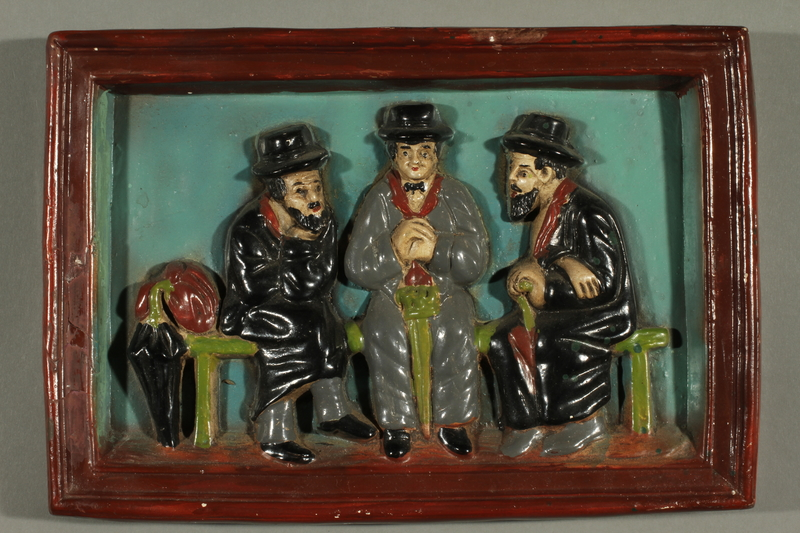 2016.184.104 front Hand painted ceramic relief of 3 Jews on a bench with their umbrellas