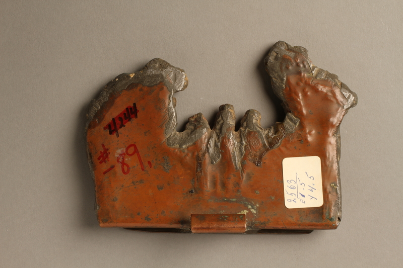 2016.184.107 back Metal doorstop with a bas relief of 3 Jews on a red bench