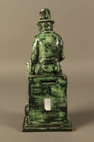 2016.184.109 back Green ceramic figurine of a Jewish peddler counting his money  Click to enlarge