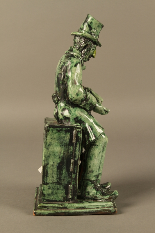 2016.184.109 right side Green ceramic figurine of a Jewish peddler counting his money
