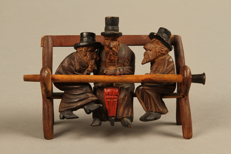2016.184.110_a-e front Tobacco pipe with decorative wooden stand of three Jews on a bench