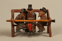2016.184.110_a-e front Tobacco pipe with decorative wooden stand of three Jews on a bench  Click to enlarge