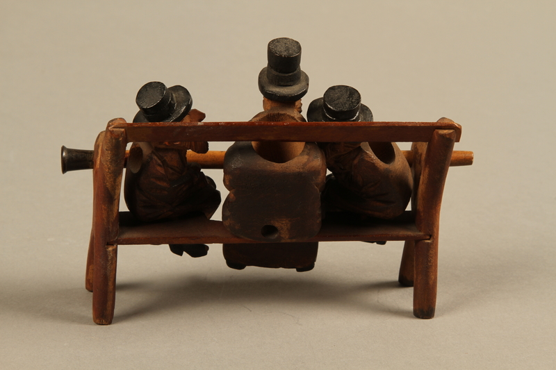 2016.184.110_a-e back Tobacco pipe with decorative wooden stand of three Jews on a bench
