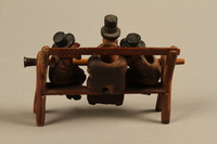 2016.184.110_a-e back Tobacco pipe with decorative wooden stand of three Jews on a bench  Click to enlarge