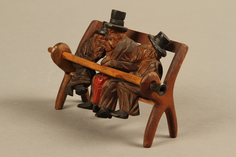 2016.184.110_a-e left side Tobacco pipe with decorative wooden stand of three Jews on a bench