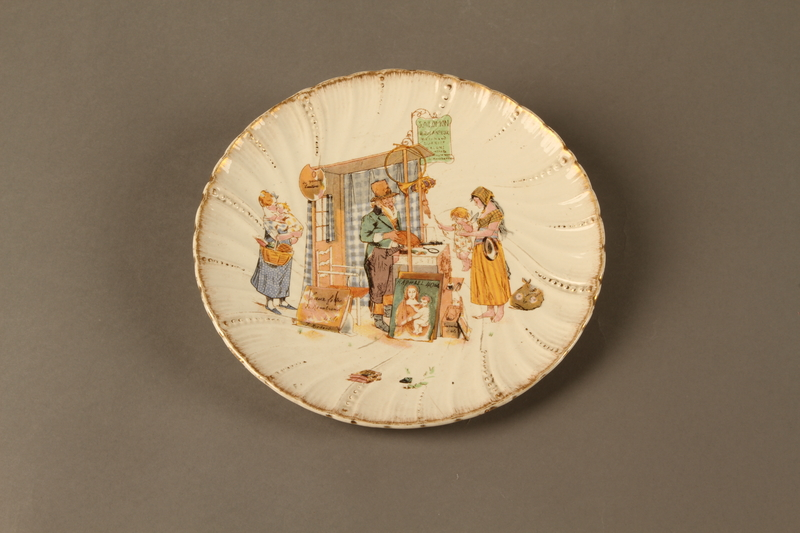 2016.184.126 front Porcelain plate with a scene of a Jewish pawn shop owner and Gentile customer