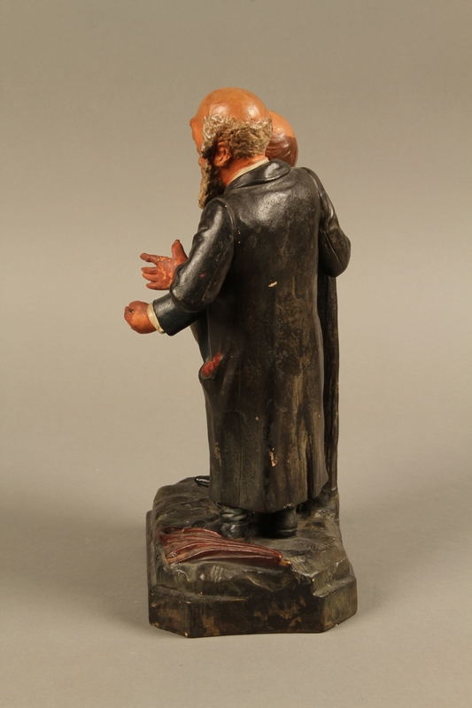 2016.184.129 left side Ceramic figure group of a poor Jew with an unhappy merchant