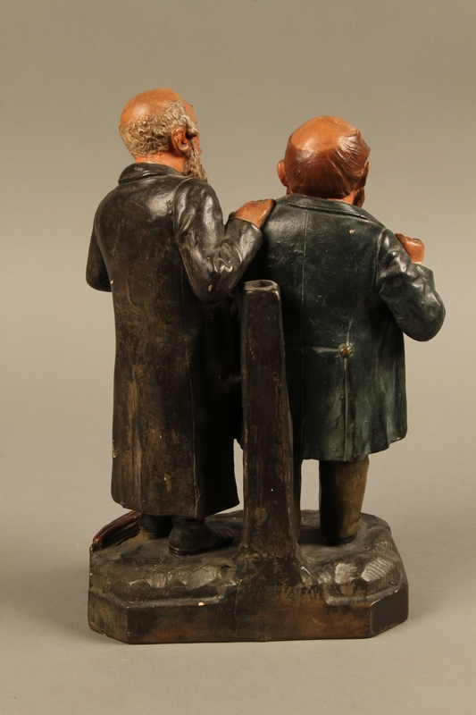2016.184.129 back Ceramic figure group of a poor Jew with an unhappy merchant