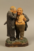 2016.184.128 front Painted figure group of a poor Jew whispering to a wealthy merchant  Click to enlarge