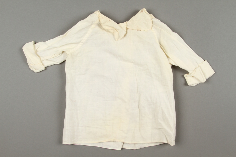 2016.181.1 front Woven shirt made by a woman for her infant nephew while in a labor camp