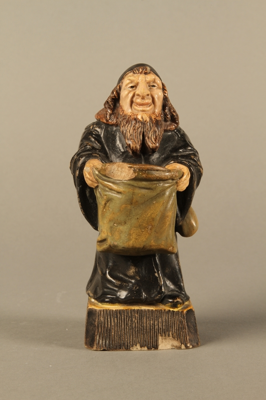 2016.184.133 front Ceramic match holder of a Jew holding out a bag