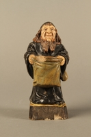 2016.184.133 front Ceramic match holder of a Jew holding out a bag  Click to enlarge