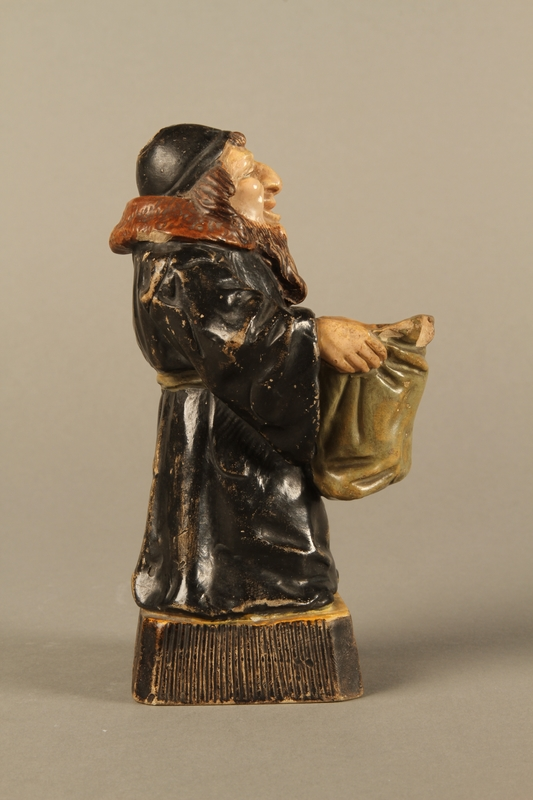 2016.184.133 right side Ceramic match holder of a Jew holding out a bag
