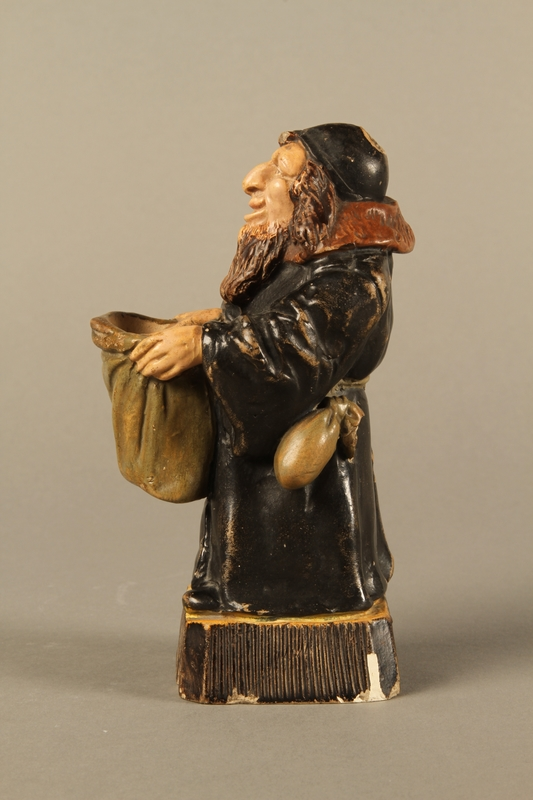 2016.184.133 left side Ceramic match holder of a Jew holding out a bag