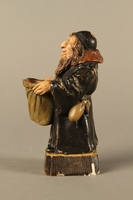 2016.184.133 left side Ceramic match holder of a Jew holding out a bag  Click to enlarge