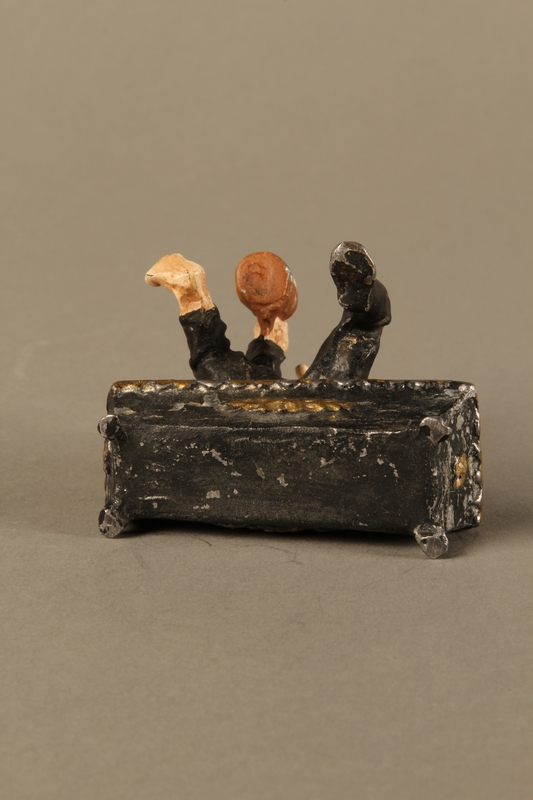 2016.184.134 _a-b bottom Painted metal figurine of a drunken Jewish man in a trough