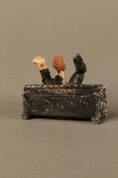 2016.184.134 _a-b bottom Painted metal figurine of a drunken Jewish man in a trough  Click to enlarge
