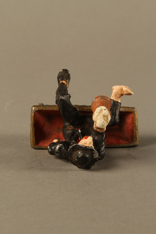 2016.184.134 _a-b top Painted metal figurine of a drunken Jewish man in a trough
