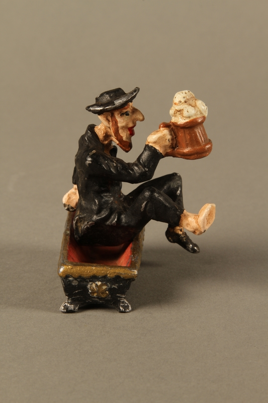 2016.184.134 _a-b right side Painted metal figurine of a drunken Jewish man in a trough