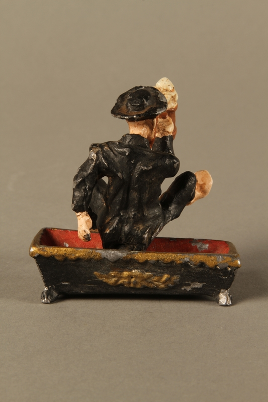 2016.184.134 _a-b back Painted metal figurine of a drunken Jewish man in a trough