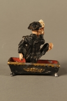 2016.184.134 _a-b back Painted metal figurine of a drunken Jewish man in a trough  Click to enlarge