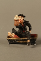 2016.184.134 _a-b front Painted metal figurine of a drunken Jewish man in a trough  Click to enlarge