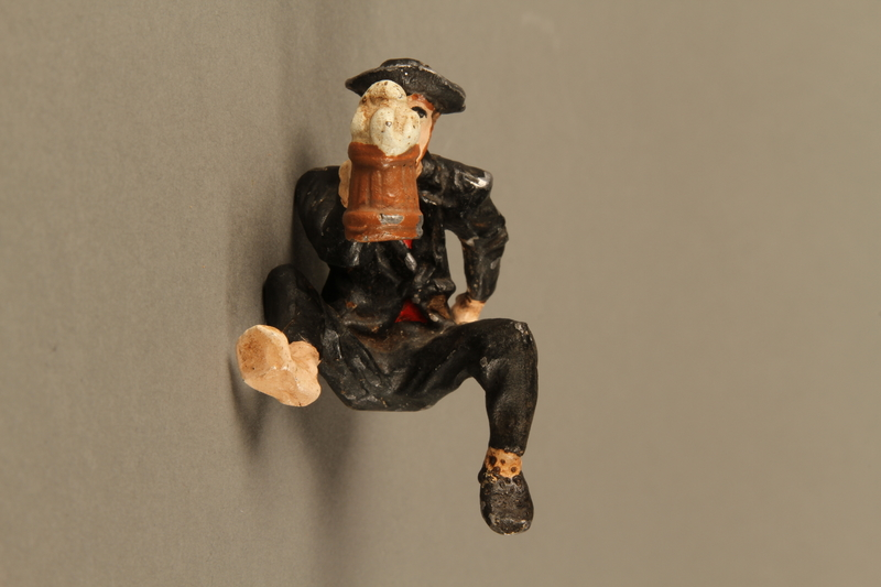 2016.184.134_a front Painted metal figurine of a drunken Jewish man in a trough