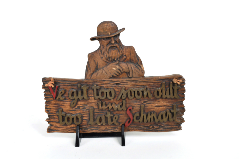 Wooden plaque of a Jew and a sign with a folk saying