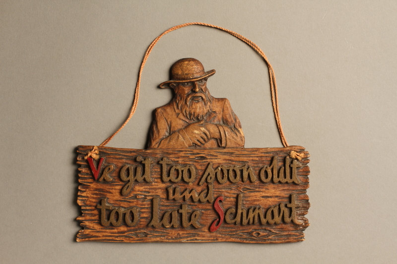 2016.184.138  front Wooden plaque of a Jew and a sign with a folk saying